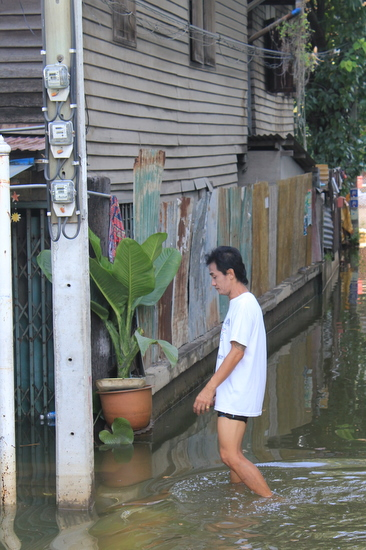 Man walks through flooded soi in Sam Sen.