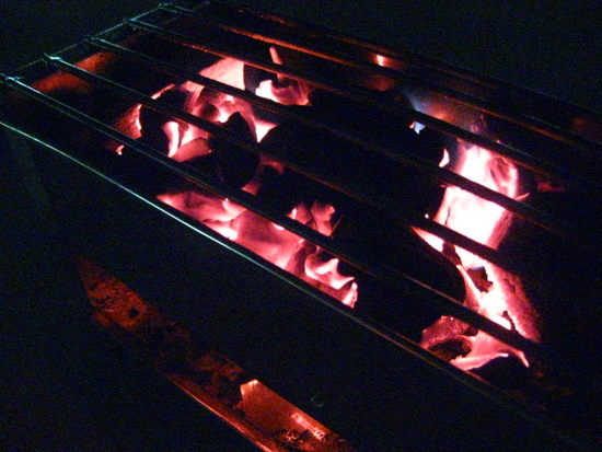 Coals glowing in the velvet night.