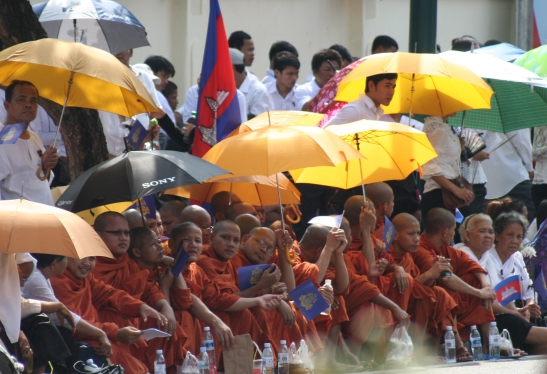 Monks wait for the cortege to pass