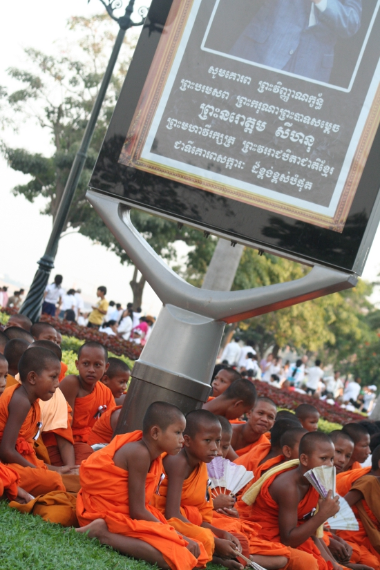 Young monks gather under a tribute poster to King Sihanouk