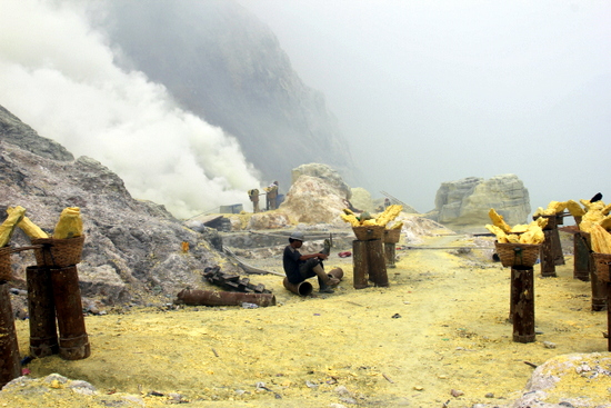 Men hacking away at chunks of sulphur in the crater at Kawah Ijen