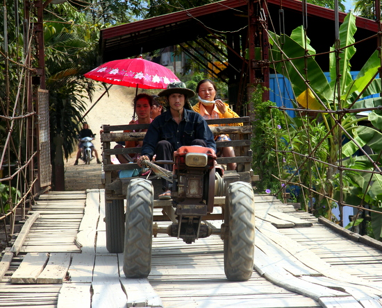 Families go about their business in Vang Vieng despite the tourist masses