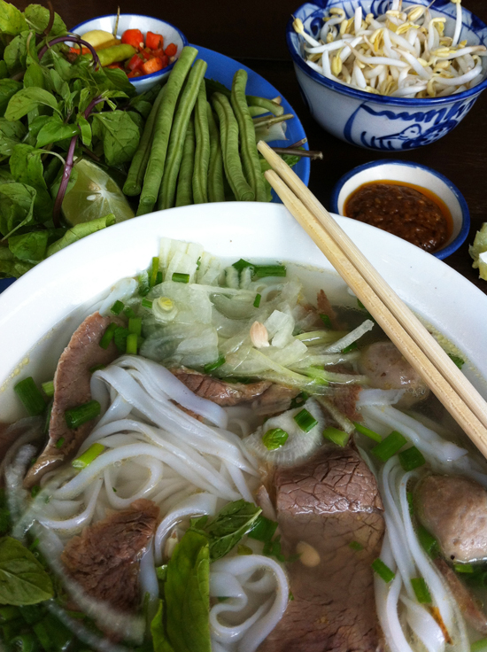 Lao pho is always served with a plate of herbs, greens and plenty of chilli