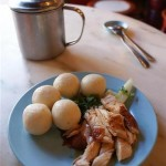Chicken rice balls and a pot of chili sauce.