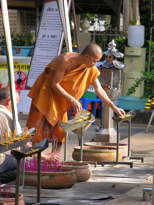 A Forest Tradition monk removes wax from candlesoffered by visitors at Wat Pa Suthawat.