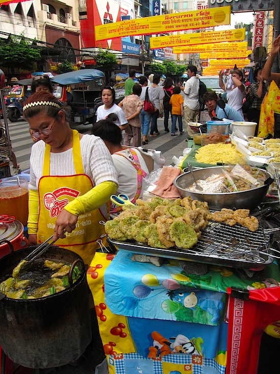 Frying up veggie rice cakes street side in Chinatown.